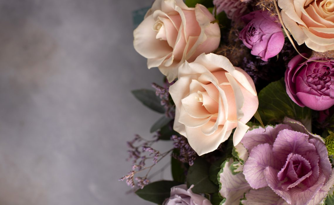 flower border of assorted fresh flowers on a gray background. horizontal image, copy space, top view
